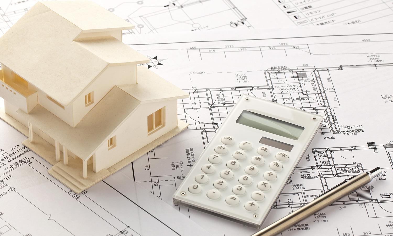 家の模型と電卓と設計図